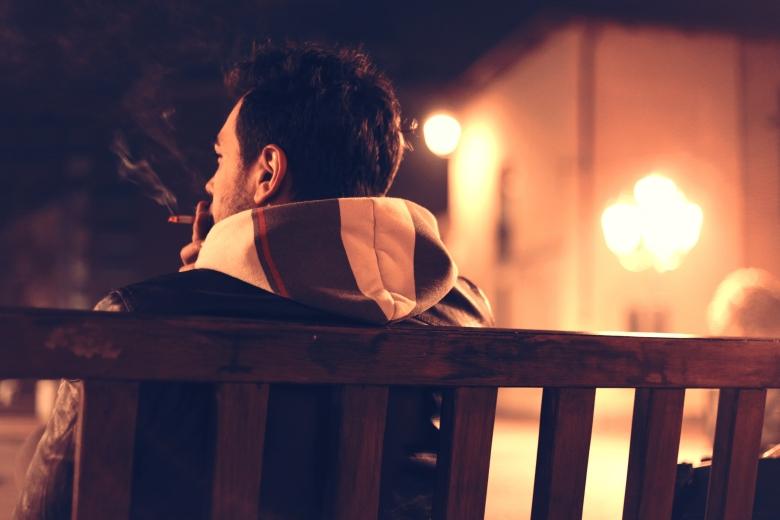 mies polttamassa tupakkaa